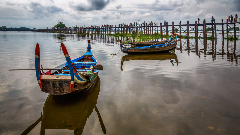 Two boats sit on the lake near Mandalay as Om Pei bridge stretches out to the other side.